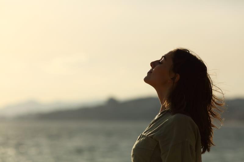 woman breathing deeply by the ocean